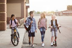 Group of school kids talking and walking home from school together. Diverse group of school kids talking and walking home from school together. Full length stock photography