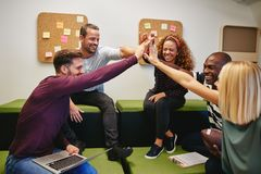 Diverse group of smiling designers high fiving in an office. Diverse group of smiling designers sitting on a sofa in a modern office high fiving together stock photography