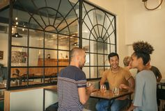 Diverse young friends enjoying drinks together in a bar. Diverse group of smiling young friends sitting together at a table in a trendy bar having drinks and royalty free stock images
