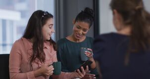 Diverse group of three happy businesswomen drinking coffee,looking at smartphone and talking at work