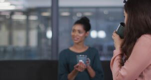 Diverse group of three happy businesswomen drinking coffee and talking at casual office meeting