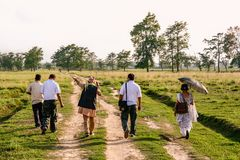 Diverse group walking through a field royalty free stock images