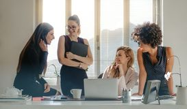 Diverse group of women having a break in office. Group of multi-ethnic businesswoman having a casual discussion in office. Group of four women talking during royalty free stock images