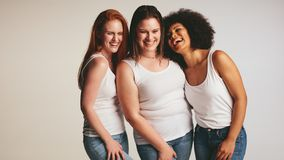 Diverse group of women laughing together. On white background. Females in casuals looking happy together stock images