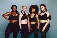 Diverse group of women in sportswear. Group of women of different race and body size dressed in sportswear standing together against grey background. Diverse royalty free stock images