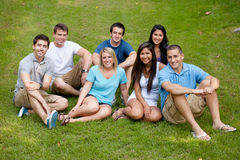 Diverse group of young adults. A diverse group of young adults sitting on the grass at a park Royalty Free Stock Photo
