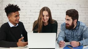 Diverse group of young entrepreneurs discussing business using laptop computer in office. Two men are arguing while. Young attractive woman is trying to stop stock footage