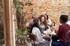 Female friends chatting over coffee in a trendy cafe courtyard stock photos