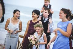 Diverse guests enjoy beach wedding party stock image