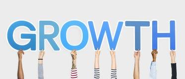 Diverse handen die blauwe brieven steunen die de woordgroei vormen stock afbeeldingen