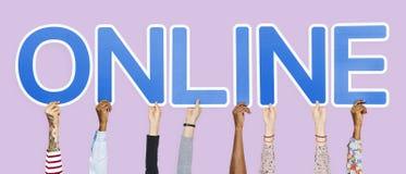 Diverse handen die blauwe brieven steunen die het woord online vormen stock foto