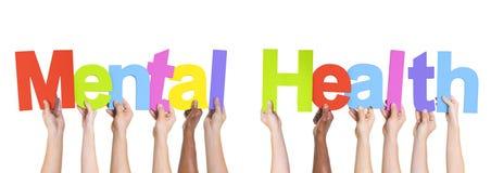 Diverse Handen die de Woorden Geestelijke Gezondheid houden Stock Foto's