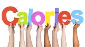 Diverse Handen die de Word Calorieën houden stock foto