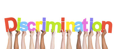 Diverse Hands Holding the Word Discrimination Royalty Free Stock Image