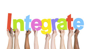 Diverse Hands Holding the Word Integrate.  Stock Photos