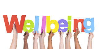 Diverse Hands Holding The Word Wellbeing.  stock photo