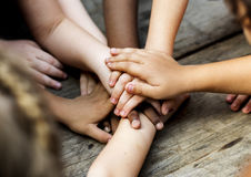 Diverse hands are join together on the wooden table Stock Images