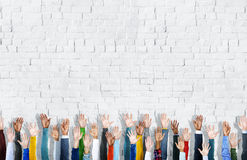 Diverse Hands Raised on a Brick Wall Background Royalty Free Stock Photography