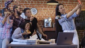 Cheerful colleagues taking selfie with pizza royalty free stock photography
