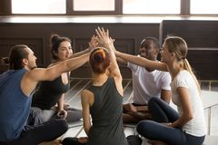Diverse happy yogi people reach hands to give high five. Sitting on mats at yoga seminar training, multiracial friends group celebrating unity in fitness goals stock photo