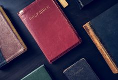 Diverse holy bibles on black background stock images