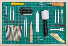 Diverse hulpmiddelen voor leatherwork op self-healing mat stock afbeeldingen