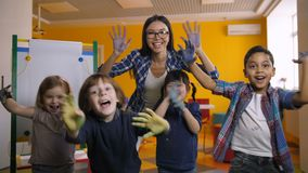 Diverse jonge geitjes die die handen tonen met verf worden geschilderd stock video