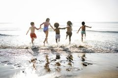 Diverse kids running at the beach royalty free stock photos
