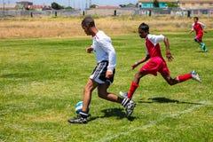 Diverse kinderen die voetbalvoetbal spelen op school royalty-vrije stock fotografie