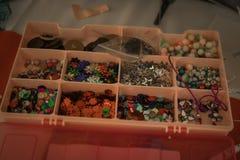 Diverse kleine punten voor het scrapbooking in een roze plastic doos stock afbeelding