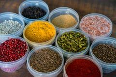 Diverse kleurrijke kruiden in plastic containers Stock Foto's