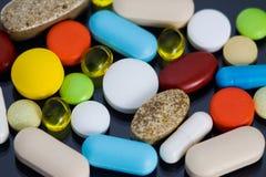 Diverse kleurrijke pillen op zwarte achtergrond Royalty-vrije Stock Foto's