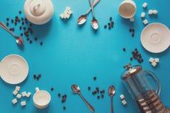 Diverse koffie die toebehoren maken: Franse koffiepers, koppen, schotels, koffiebonen, lepels en suiker op blauwe document achter stock foto