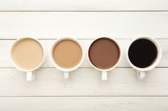 Diverse koffiekoppen op witte houten, hoogste mening Stock Fotografie