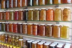 Diverse kruiken met fruitjam op glasplanken stock fotografie