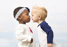 Diverse Little Kids First Kiss. Two cute little kids kissing. One african american child and one caucasian. Diversity Stock Photography