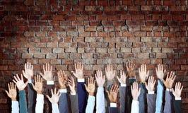 Diverse mani di affari sollevate sul muro di mattoni Immagine Stock Libera da Diritti