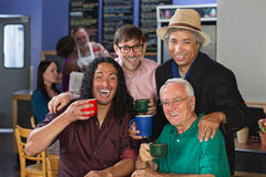 Diverse Men Celebrating. Diverse group of men celebrating in coffee house Stock Image