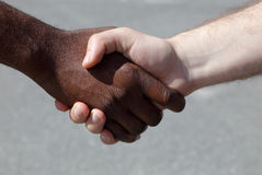 Diverse men shaking hands. African and Caucasian men shaking hands outdoors Stock Images
