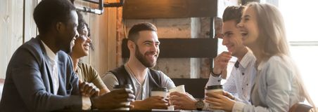 Diverse millennial cheerful friends spending free time together at cafe royalty free stock image