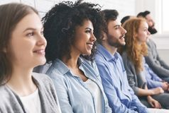Diverse millennial group sitting in row, waiting for something. In queue, empty space royalty free stock images