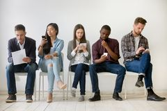 Diverse millennial people waiting in queue holding resumes using. Diverse millennial unemployed people waiting in queue preparing for job interview, multi-ethnic Stock Photos