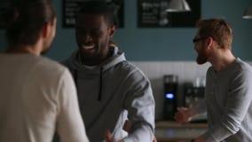 Diverse millennial vriendenmensen die met omhelzingen handdruk in koffie begroeten stock video