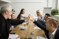 Diverse motivated young and senior business people giving high f. Diverse young and senior business people giving high five building successful team at meeting Royalty Free Stock Image