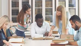 Diverse multiracial students spending leisure time in library with big old book stock video footage