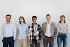 Diverse multiracial team of young people posing near wall royalty free stock image