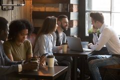 Diverse multiracial young people talking drinking coffee in cozy. Diverse multiracial young people talking drinking coffee using devices in cozy coffeehouse royalty free stock photography
