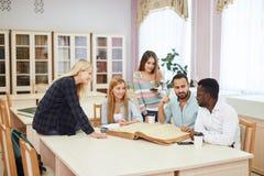 Diverse multiraciale studenten die vrije tijd in bibliotheek met groot oud boek doorbrengen royalty-vrije stock foto
