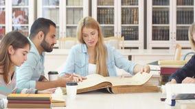 Diverse multiraciale studenten die vrije tijd in bibliotheek met groot oud boek doorbrengen stock video