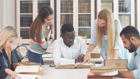 Diverse multiraciale studenten die vrije tijd in bibliotheek met groot oud boek doorbrengen stock videobeelden